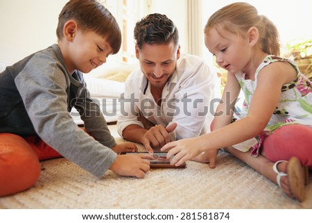 Father with son and daughter sitting on floor using digital tablet indoors. Happy young family together at home using touchpad computer. Young man teaching his children how to use digital tablet. - stock photo