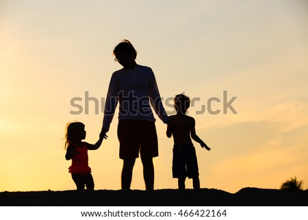 father with son and daughter walking at sunset