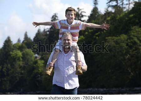 father with son on his shoulders at a beach - stock photo