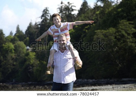 father with son on his shoulders at a beach