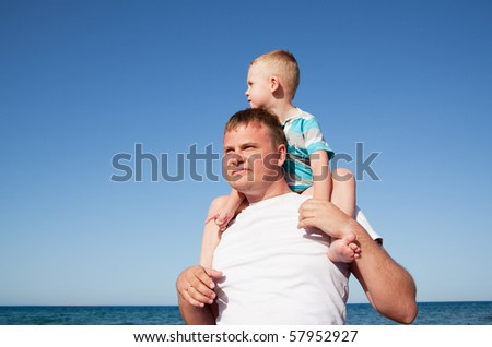 father with son on shoulders, sunny day, blue sky