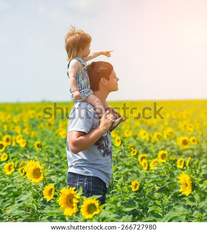 Father with son on the sunflower field - stock photo
