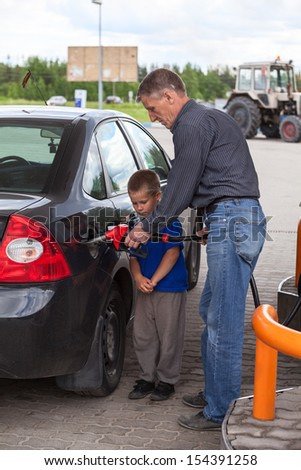 Father with son refueling car on gas station together - stock photo