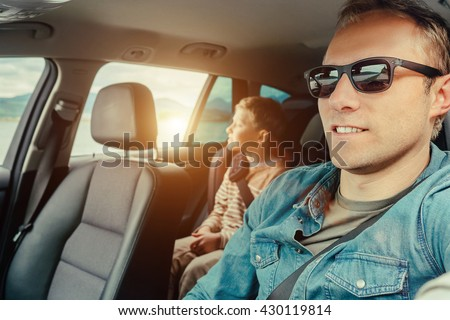 Father with son sit in car - stock photo