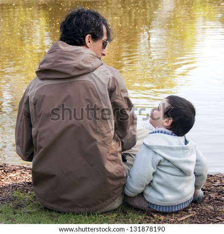 Father with son sitting by a river or a lake talking to each other, back view. - stock photo