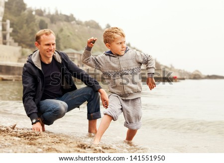 Father with son throw pebbles into the sea - stock photo