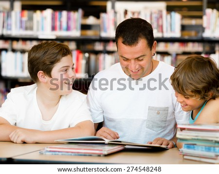 Father with sons in library with books - stock photo