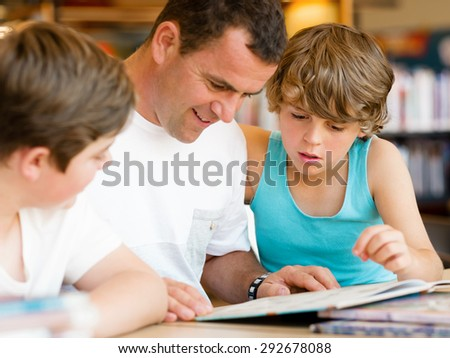 Father with sons in library with books