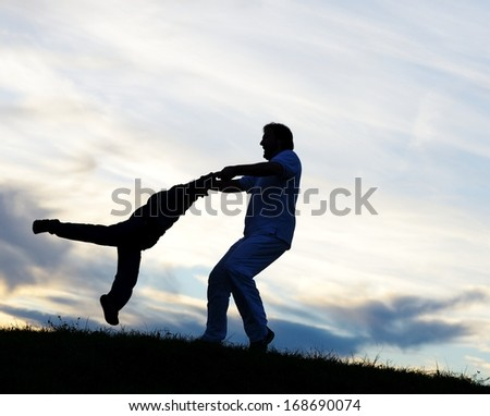 Father with sons playing on sunset meadow - stock photo