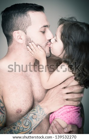 Father with tattoos kissing his Baby girl, color processed  - stock photo