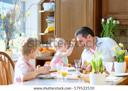 Father with teenager son and toddler daughter eating eggs during family breakfast on Easter day sitting together in sunny kitchen. Selective focus on girl and man. - stock photo