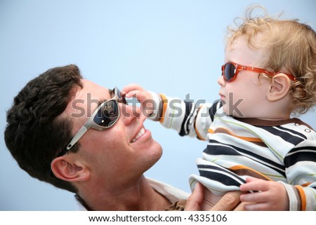 father with the child in the sunglasses against the background of the sky - stock photo