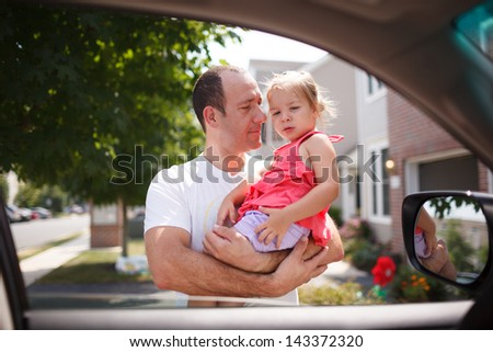 Father with toddler girl daughter standing outdoors, framed in open car window. - stock photo