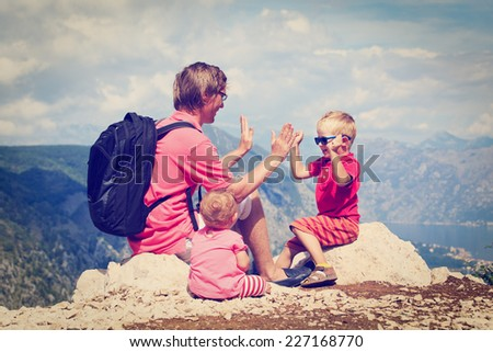 father with tow kids having fun on vacation in mountains - stock photo
