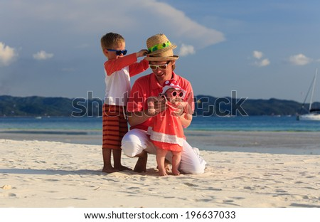 father with two kids having fun on tropical beach