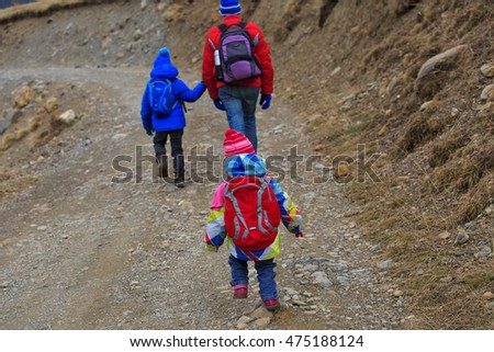 father with two kids hiking in winter mountains