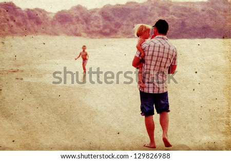 father with two kids on vacation at sea on sunset colors. Photo in old color image style. - stock photo