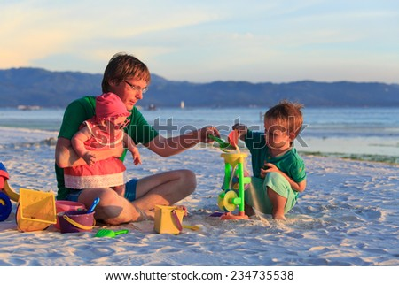 father with two kids playing on tropical sand beach