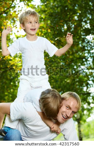 Father with two small sons frolic in park - stock photo