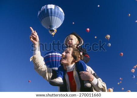 Father with young son on his shoulders, Albuquerque's Hot Air Balloon Festival, New Mexico - stock photo