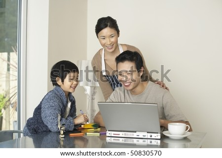 Father working on computer at dining room table, wife and son watching - stock photo