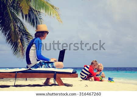 father working on laptop while kids play with sand on beach
