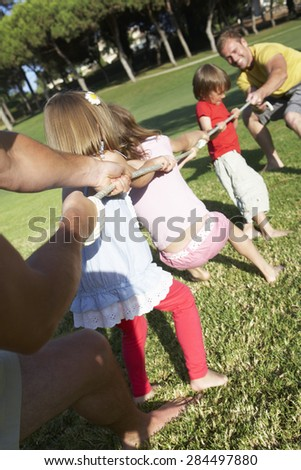 Fathers And Children Playing Tug Of War - stock photo