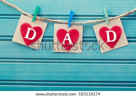 Fathers day message on felt hearts over blue wooden board - stock photo