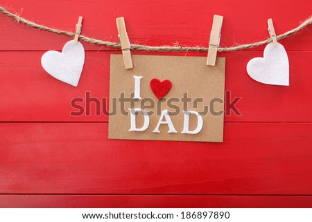 Fathers day message with felt hearts hanging with clothespins over red wooden board  - stock photo