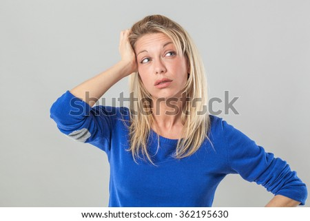 fatigue or hangover concept - tired young blond woman with bags touching her head for headache,studio shot - stock photo