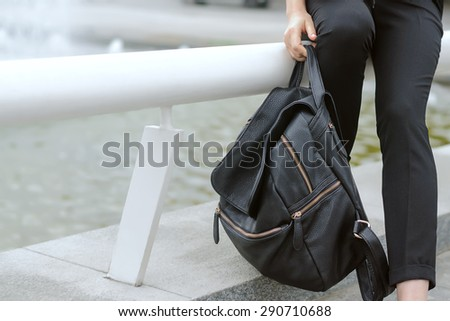 Fatigue, tiredness concept. A girl holding a heavy backpack in her hand