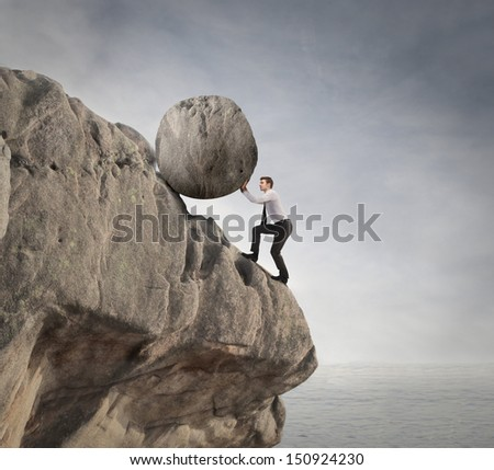 fatigued businessman supports large boulder - stock photo
