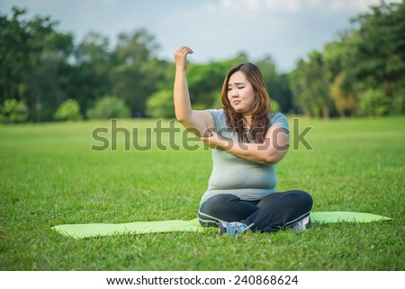 fatty woman checking her fat arm in the garden