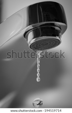 Faucet and falling water drop - stock photo