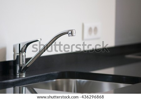 Faucet in the new modern kitchen, neutral colors, shallow depth of field