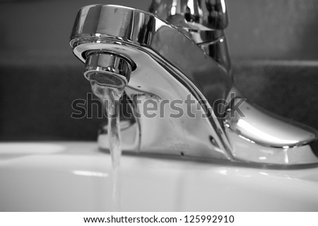 Faucet running in black and white