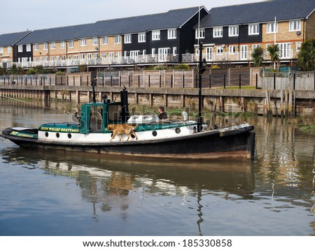 FAVERSHAM, KENT/UK - MARCH 29 : Small tug towing Cambria Thames sailing barge in Faversham Kent on March 29, 2014. Unidentified man. - stock photo