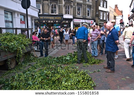 FAVERSHAM, UK-SEPTEMBER 1: Visitors to the famous annual  Hop Festival in Faversham's town centre buy sacks of hops brought in by farmers to decorate their homes. September 1, 2013 , Faversham,  UK. - stock photo