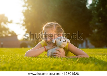 Favorite child's toy is embraced by its master. Sunshine is everywhere. Spring time came. Sincere smile of a little caucasian girl. - stock photo