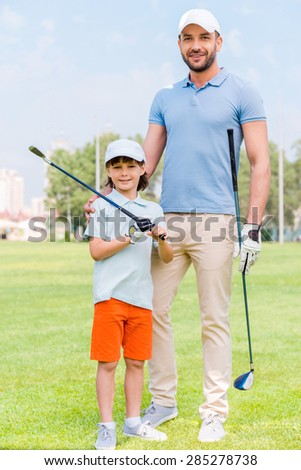 Favorite family game. Cheerful young man embracing his son while standing on the golf course - stock photo