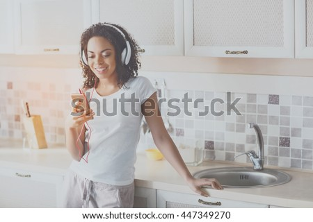 Favorite one. Happy and content young woman enjoying her music at home standing in the kitchen and holding her phone with a smile of bliss - stock photo
