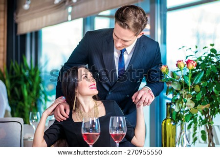 Favorite person surprises. Romantic dinner in the restaurant. Young couple sitting at a table in the restaurant until the guy opened the girl her eyes with his hands - stock photo