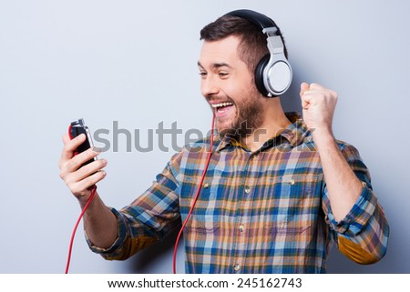 Favorite track. Handsome young man in headphones holding mobile phone and smiling while standing against grey background