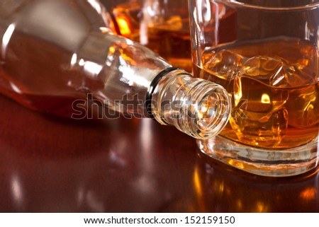 Favorite whiskey with ice cubes and a bottle on the bar - stock photo