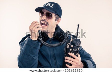 FBI agent man with mustache in heavy coat talking on vintage radio reporting in during situation - stock photo
