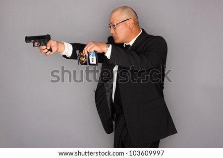 FBI Agent with gun and holding a badge.