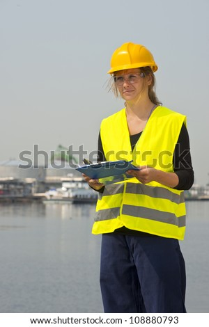 Feamale engineer with hard hat, safety goggles and a safety vest in a harbor district
