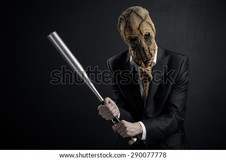 Fear and Halloween theme: a brutal killer in a mask holding a bat on a dark background in the studio - stock photo