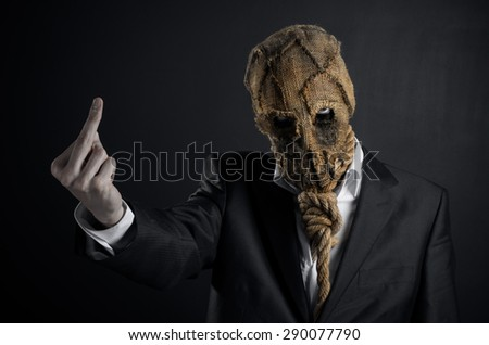Fear and Halloween Theme: creepy killer in a mask on a dark background in the studio - stock photo