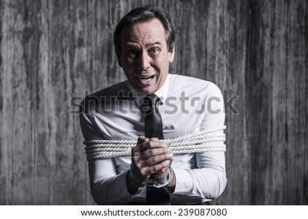 Fear and hopelessness. Shocked tied up businessman asking help while sitting at the chair with dirty wall  in the background - stock photo